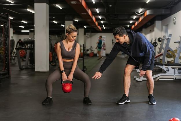 Fitness paar in sportkleding gehurkt met gewichten en squats in de sportschool doen. een personal trainer in de sportschool corrigeert de squats van een jonge atleet.