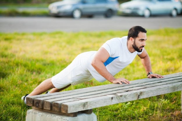 Fitness. push-up oefening fitness man training wapens spieren op outdoor gym