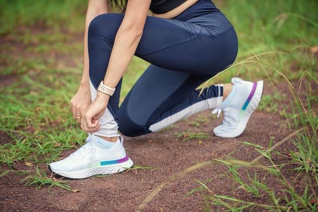 Fitness runner-atleet die naar muziek luistert in een koptelefoon van een mobiele smartphone-app die de voortgang bijhoudt. training wellness-concept.