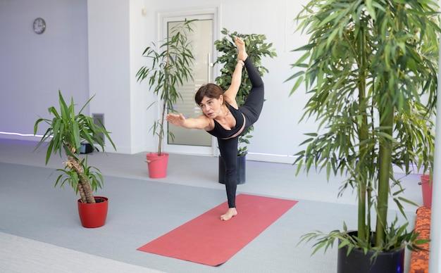 Fitness senior vrouw doet stretching in de sportschool