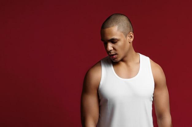 Fitness, sport, actief en gezond levensstijlconcept. stijlvolle jonge halfbloed atletische 20-jarige man met gespierde schouders staan ?? geïsoleerd op rode copyspace studio muur, naar beneden te kijken