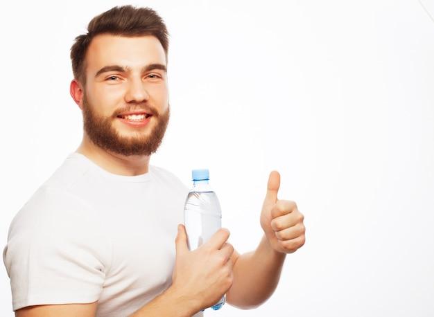 Fitness, sport en lifestyle concept. lachende gespierde sportieve man met wit overhemd met fles water geïsoleerd op wit.