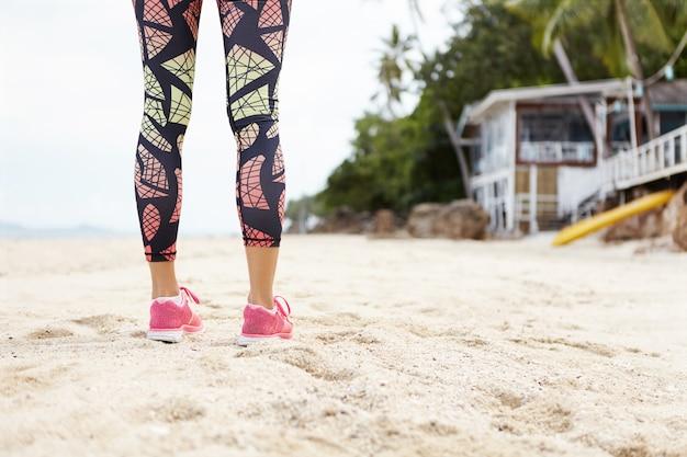 Fitness, sport en mensen. vrouwelijke jogger met gespierde atletische benen in kleurrijke beenkappen staande op zandstrand tijdens haar buiten joggen oefeningen.