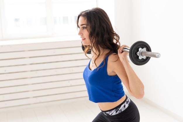 Fitness, sport en mensenconcept - glimlachende sportieve vrouw met barbell die gespleten kraakpand of uitval doet.