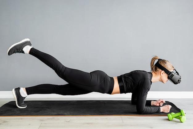 Fitness, sport en technologie. jonge atletische vrouw die virtual reality-bril doet doetplank op blauwe achtergrond