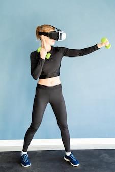 Fitness, sport en technologie. jonge atletische vrouw die vr-bril draagt die zich bij geschiktheidsmat bevindt die met dubbells uitwerkt