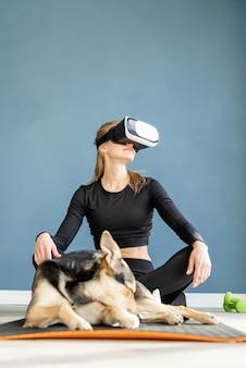 Fitness, sport en technologie. jonge atletische vrouw vr bril zittend op fitness mat met hond