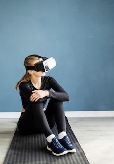Fitness, sport en technologie. jonge atletische vrouw vr bril zittend op fitness mat