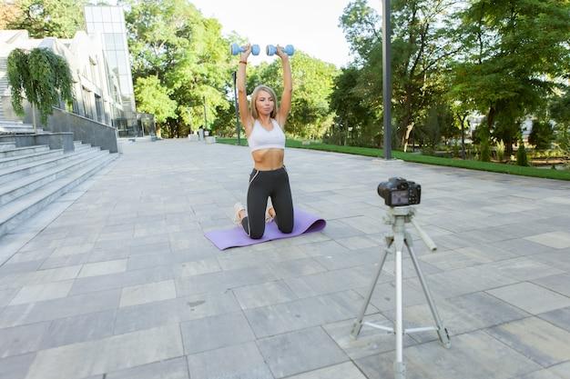 Fitness, sport en video bloggen concept. vrouwelijke sportblogger met camera op statief die outdoor fitnesstraining met halters opneemt