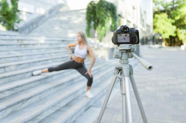 Fitness, sport en video bloggen concept. vrouwelijke sportblogger met camera op statief die outdoor fitnesstraining opneemt. focus op camera