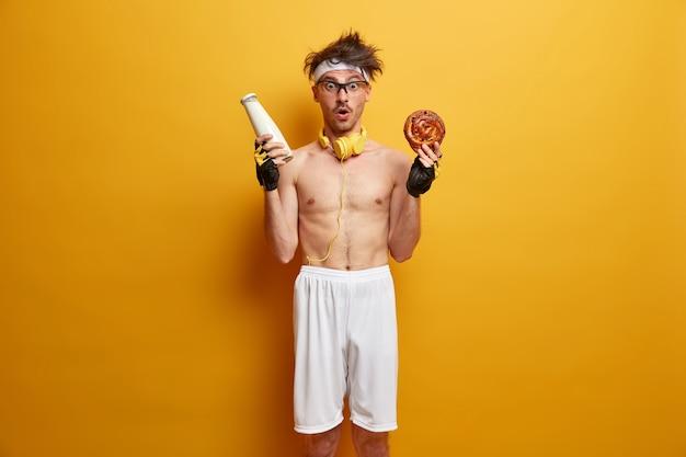 Fitness, sport, gewichtsverlies en dieetconcept. verbijsterde bodybuilder poseert met fles melk en smakelijk smakelijk broodje, draagt witte korte broek en sporthandschoenen, staat tegen gele muur