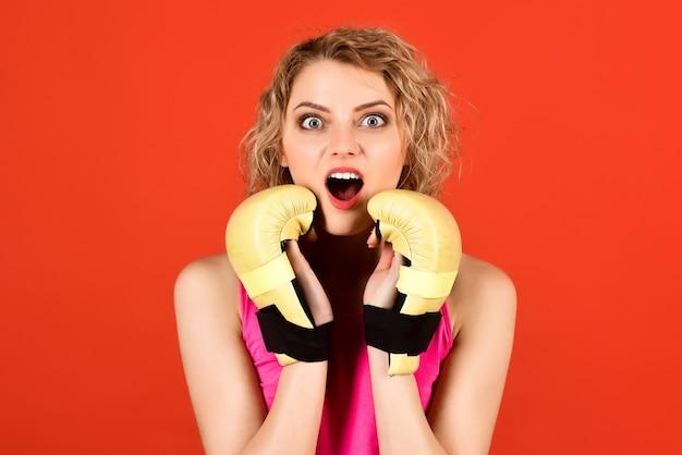 Fitness sport levensstijl gezondheid concept vrouw in sportkleding met bokshandschoenen verrast bokser meisje