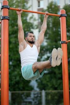 Fitness, sport, lichaamsbeweging, opleiding en levensstijl concept - jonge man buik oefening op horizontale balk in zomer park