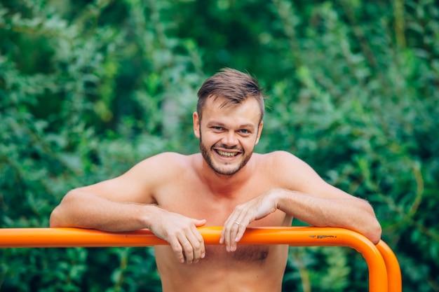 Fitness, sport, lichaamsbeweging, opleiding en levensstijl concept - jonge man doet triceps duik op parallelle staven buitenshuis. glimlach