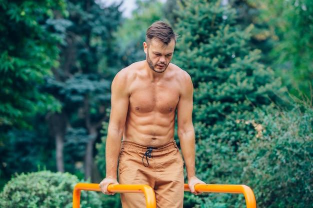 Fitness, sport, lichaamsbeweging, opleiding en levensstijl concept - jonge man doet triceps duik op parallelle staven buitenshuis.