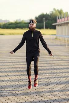 Fitness sport man springen met springtouw buitenshuis