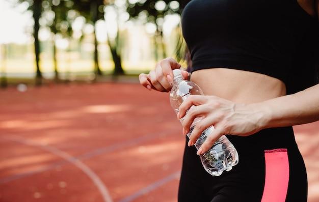Fitness sport meisje in mode sportkleding drinkwater. wereld water dag