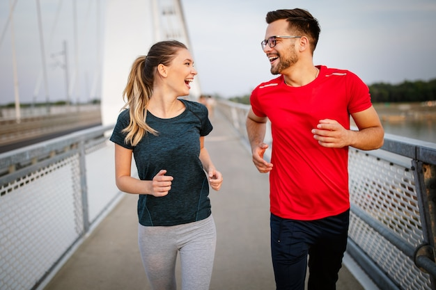 Fitness, sport, mensen, sporten en lifestyle concept. fit stel dat buiten loopt