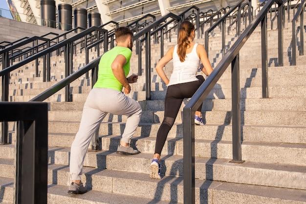 Fitness, sport, mensen, sporten en lifestyle concept - paar rennen naar boven op stadstrappen