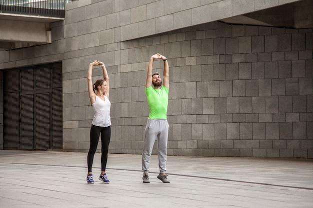 Fitness, sport, oefenen, training en mensen concept - paar doen triceps duik oefening op straat bankje.