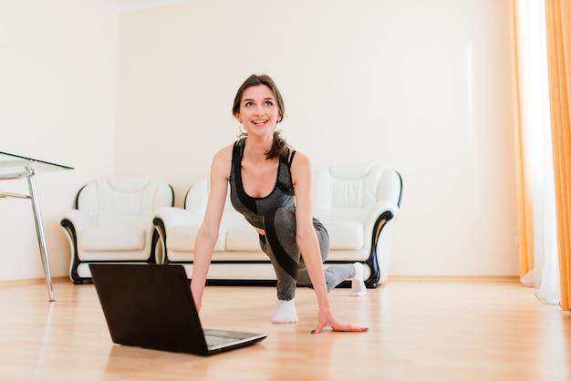 Fitness, sport, opleiding en levensstijlconcept - glimlachende vrouw die bij haar thuis opleidt