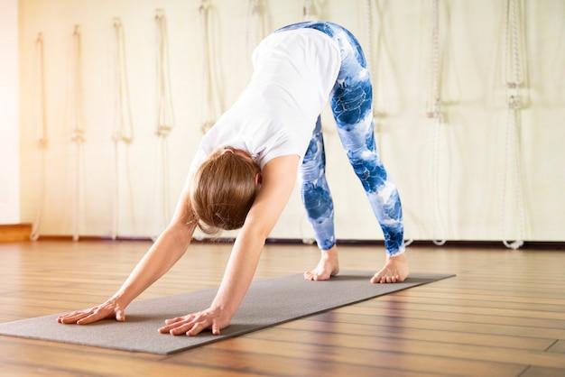 Fitness, sport, opleiding en levensstijlconcept - vrouw het uitrekken zich op mat in gymnastiek