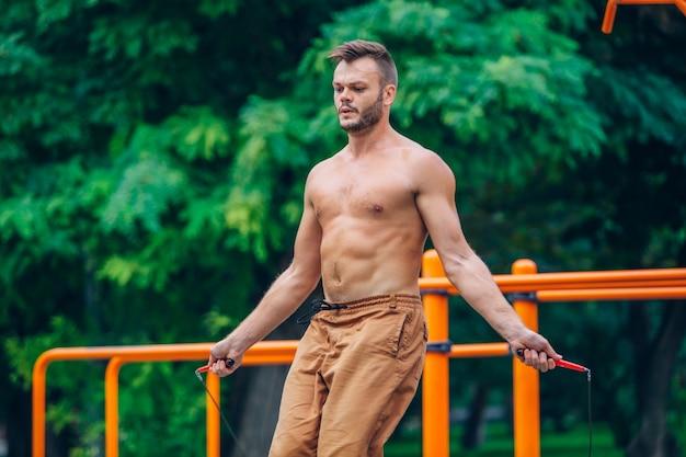 Fitness-, sport-, opleidings- en levensstijlconcept - gezonde atleet met ontbloot bovenlijf springen met springtouw buiten.