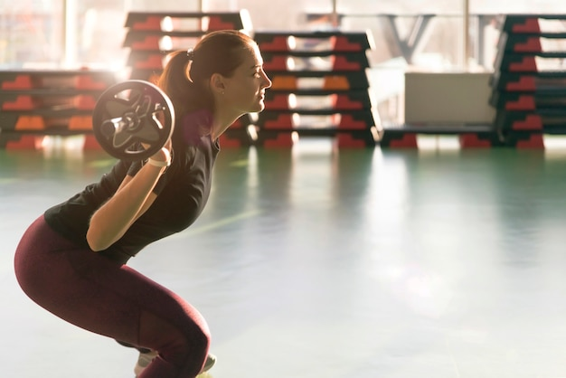 Fitness, sport, powerlifting en mensenconcept - sportieve vrouw die met barbell in gymnastiek uitoefenen