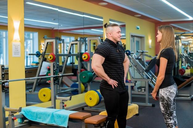 Fitness, sport, sporten, technologie en voeding concept. lachende jonge vrouw en personal trainer met smartphone in de sportschool