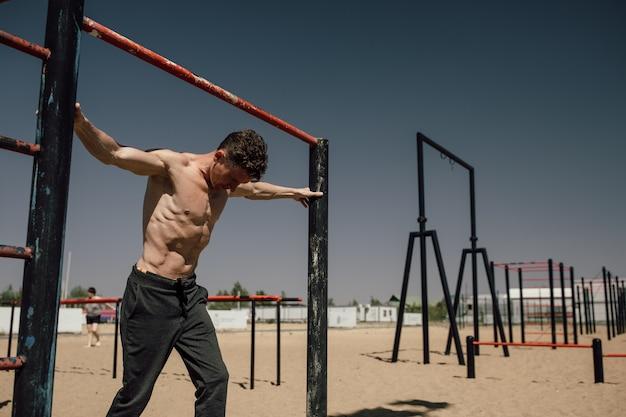 Fitness, sport, training en lifestyle concept - jonge man die handstand uitoefent op bar buitenshuis - gymnastiek. hoge kwaliteit foto