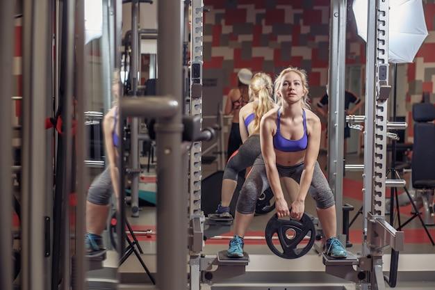 Fitness, sport, training, gym en lifestyle concept. groep lachende mensen trainen in de sportschool