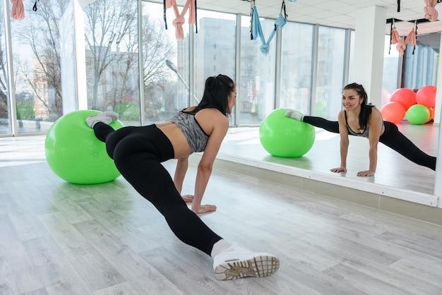 Fitness sport voor jonge vrouw die oefening doet met fit bal op sportschool. vrouwelijke training Premium Foto
