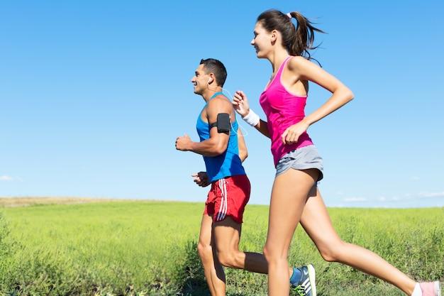 Fitness, sport, vriendschap en lifestyle concept - lachend paar samen rennen