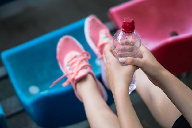 Fitness sport vrouw in mode sportkleding, de vrouw is drinkwater, fitness oefening in het stadion. buitensportkleding en -schoenen, urban style. gezond