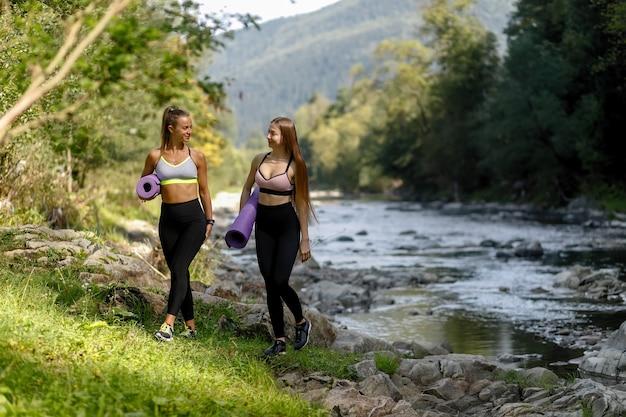 Fitness, sport, yoga en gezonde levensstijl concept - glimlachende vrienden in fitness dragen wandelen in het park met yogamatten. twee fitnessvrouwen gaan voor een yogatraining in het park.