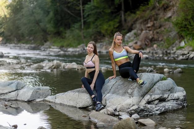 Fitness, sport, yoga en gezonde levensstijl concept - happy vriendinnen zitten in de weilanden na een training. fitness vrouwen bij elkaar zitten en ontspannen na een training.
