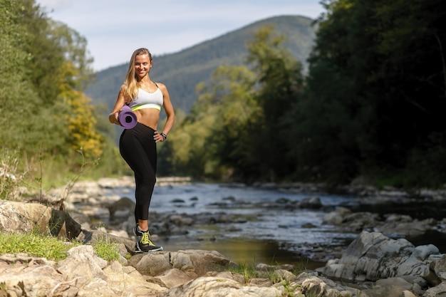 Fitness, sport, yoga en gezonde levensstijl concept - jonge vrouw met slank gezond lichaam staande met yoga mat