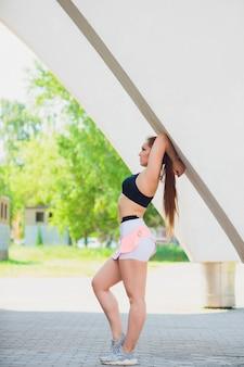 Fitness sportief meisje dat maniersportkleding over straatmuur draagt, buitensporten, stedelijke stijl. tienermodel in swagkleren die buiten stellen
