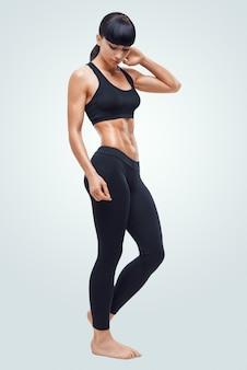 Fitness sportieve vrouw die haar goed opgeleide lichaam toont. sterke buikspieren laten zien.