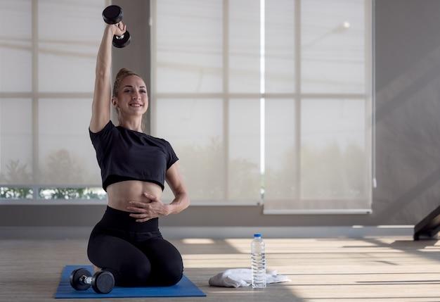 Fitness sportieve vrouw doet de oefeningen met halters, kracht en motivatie.
