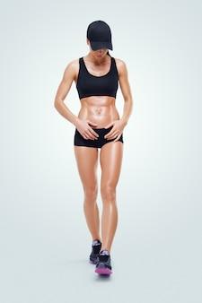Fitness sportieve vrouw op een sportkleding en baseballcap, wandelen na de training. sterke buikspieren laten zien.