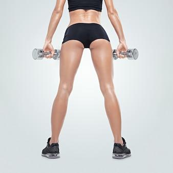 Fitness sportieve vrouw op een sportkleding in opleiding die spieren oppompt met halters achteraanzicht