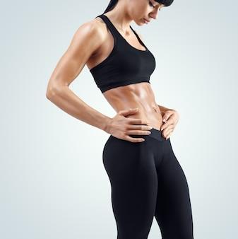 Fitness sportieve vrouw toont haar goed opgeleide lichaam geïsoleerd op een witte achtergrond. sterke buikspieren laten zien.