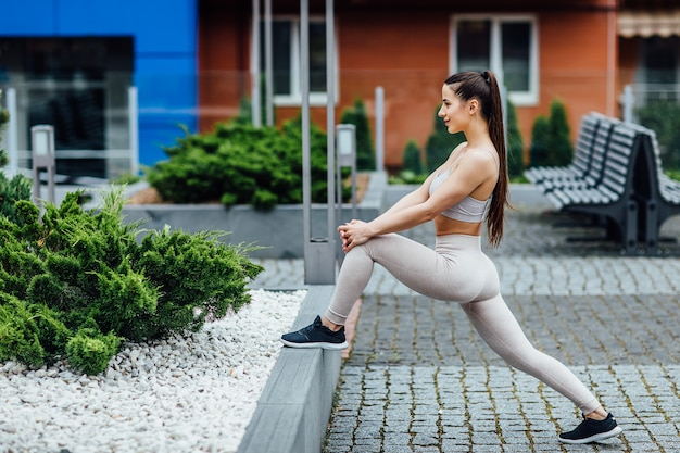 Fitness sportmeisje in maniersportkleding die yoga fitness oefening in de straat, buitensporten, fitness stijl doen.