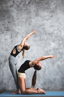 Fitness, stretching praktijk, groep van twee aantrekkelijke vrouwen trainen in sportclub