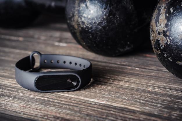 Fitness tracker en ijzeren halters op een houten achtergrond