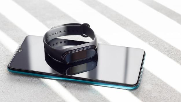Fitness tracker ligt op een smartphone met met de stralen van de ochtendzon.