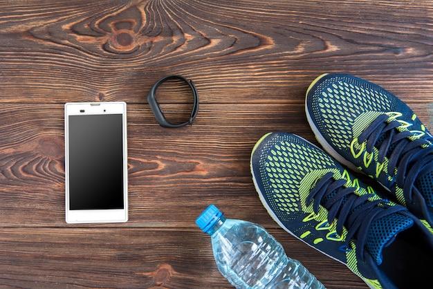 Fitness tracker, slimme telefoon en sneakers op houten tafel met kopie ruimte. gezonde levensstijl achtergrond.