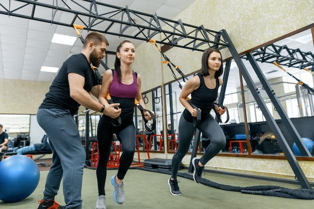 Fitness trainer coaching en het helpen van vrouwen die oefeningen doen