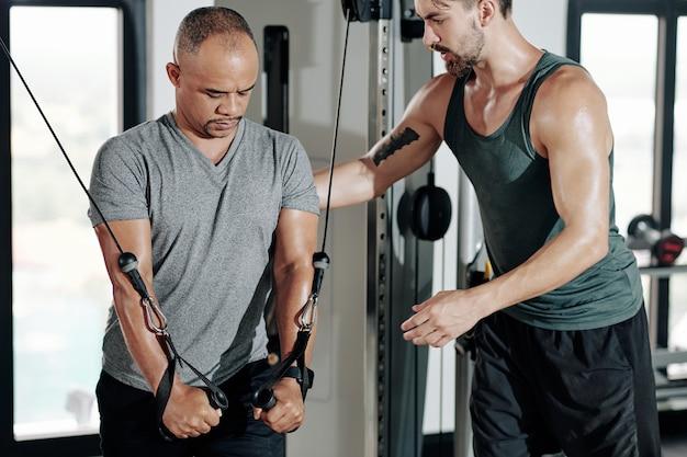 Fitness trainer die de houding van de cliënt controleert bij het doen van oefeningen in een kabeloversteekmachine om de spieren van armen en bovenborst te versterken
